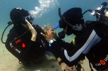 Bayu and Ming high five under water